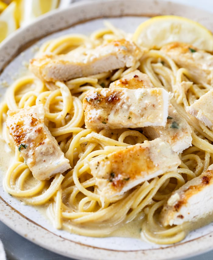 A plate with Creamy Lemon Chicken on top of Spaghetti pasta.