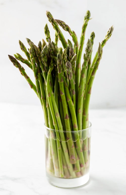 A glass of water with asparagus in it to keep it fresh.