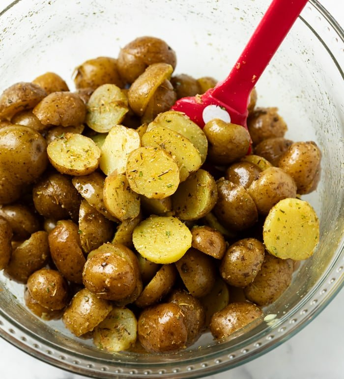 A glass bowl with potatoes tossed in seasoning and oil before being roasted.