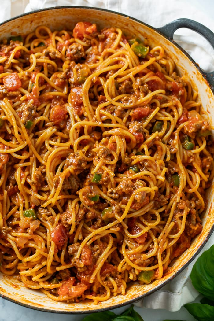A pot filled with Spaghetti in meat sauce with bell peppers and diced tomatoes.