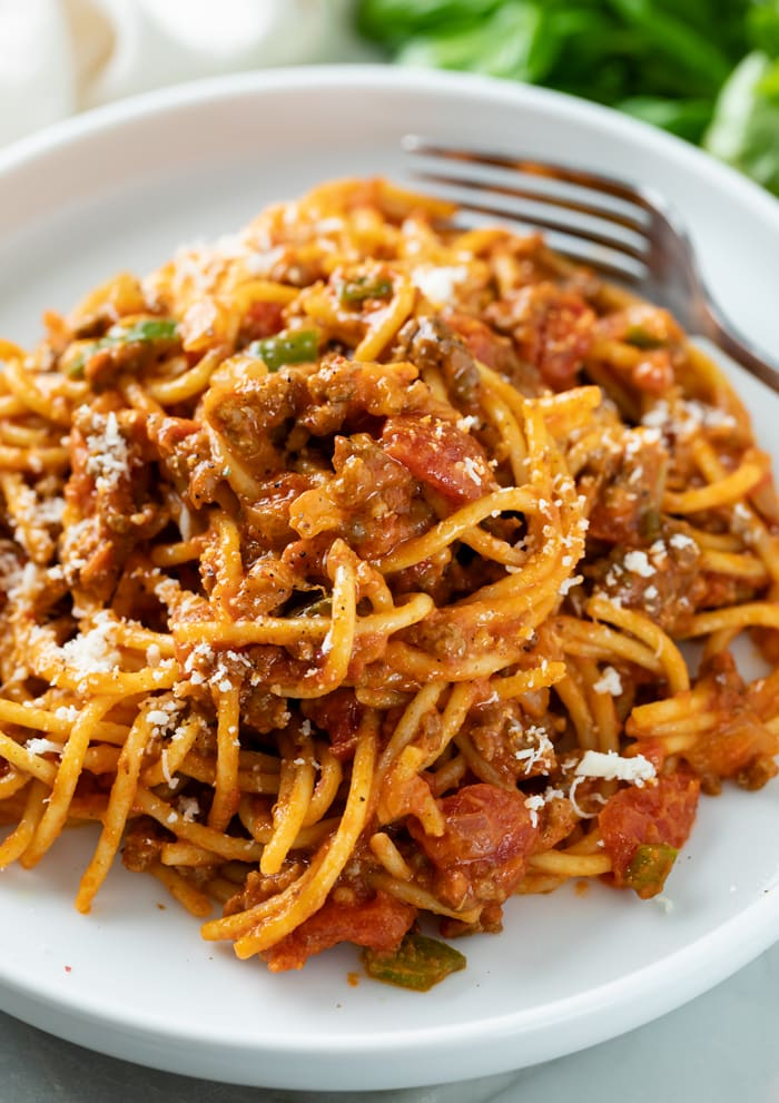 A white plate topped with One Pot Spaghetti in meat sauce.