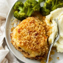 Parmesan Crusted Chicken with broccoli and mashed potatoes on a white plate with a fork.