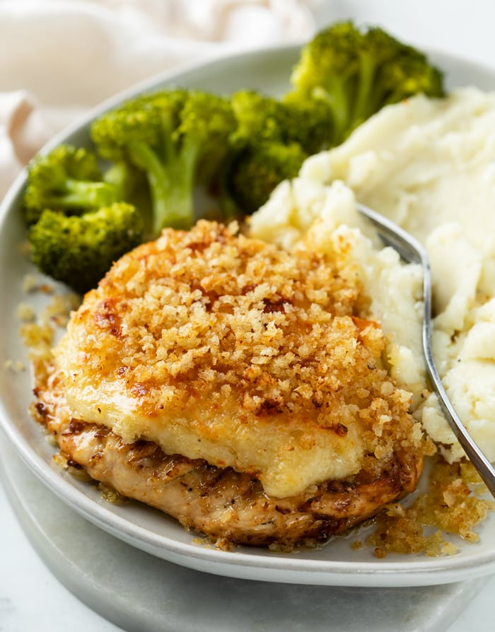 A white plate with Parmesan Crusted Chicken and Broccoli in the background.
