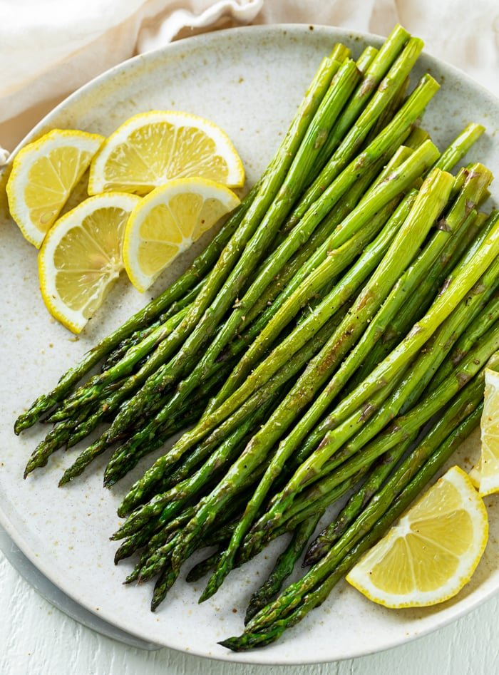 A white plate with roasted asparagus on top with sliced lemons.
