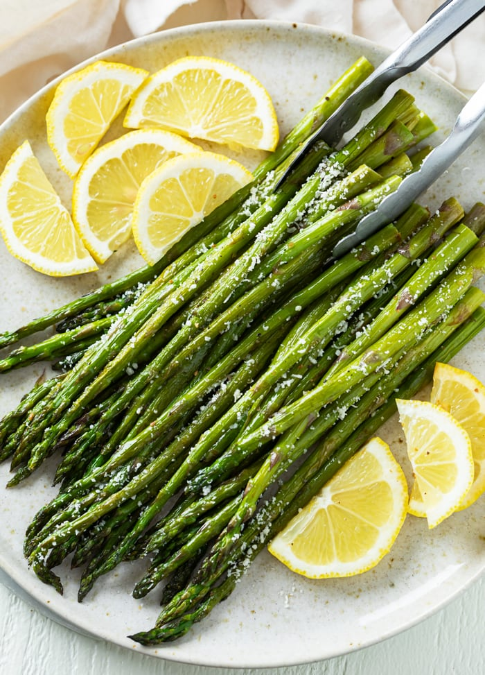 Kitchen tongs picking up a stack of Roasted Asparagus topped with grated Parmesan Cheese.