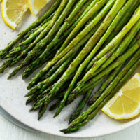 A plate topped with roasted asparagus and lemon wedges.