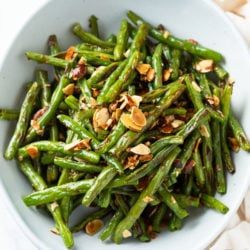 A white bowl filled with roasted green beans with thinly sliced almonds on top.