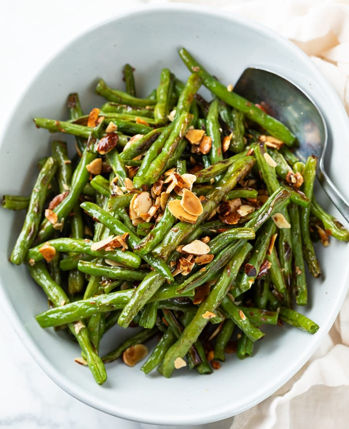 A white bowl with roasted green beans and almonds with a spoon on the side.