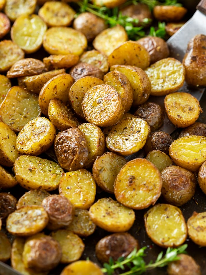 Roasted potatoes with seasoning on top on a baking sheet with fresh thyme.