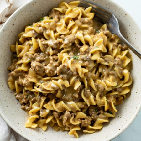 A bowl filled with creamy Beef and Noodles with a fork.