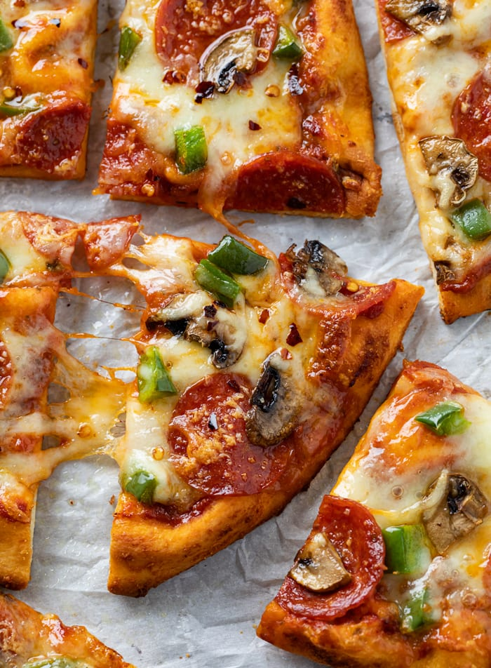 A slice of Naan Pizza with mushrooms, pepperoni, and peppers.