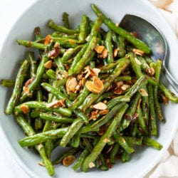 A white bowl of roasted green beans topped with sliced almonds.