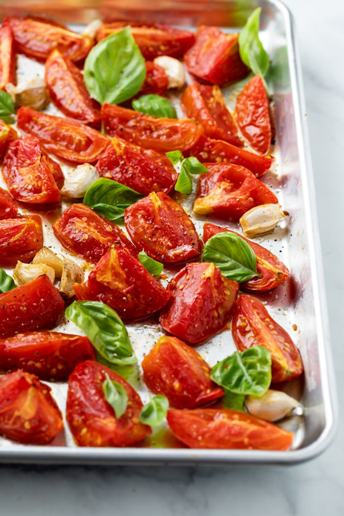 A rimmed baking sheet with roasted tomatoes and basil on top with salt and freshly cracked pepper.