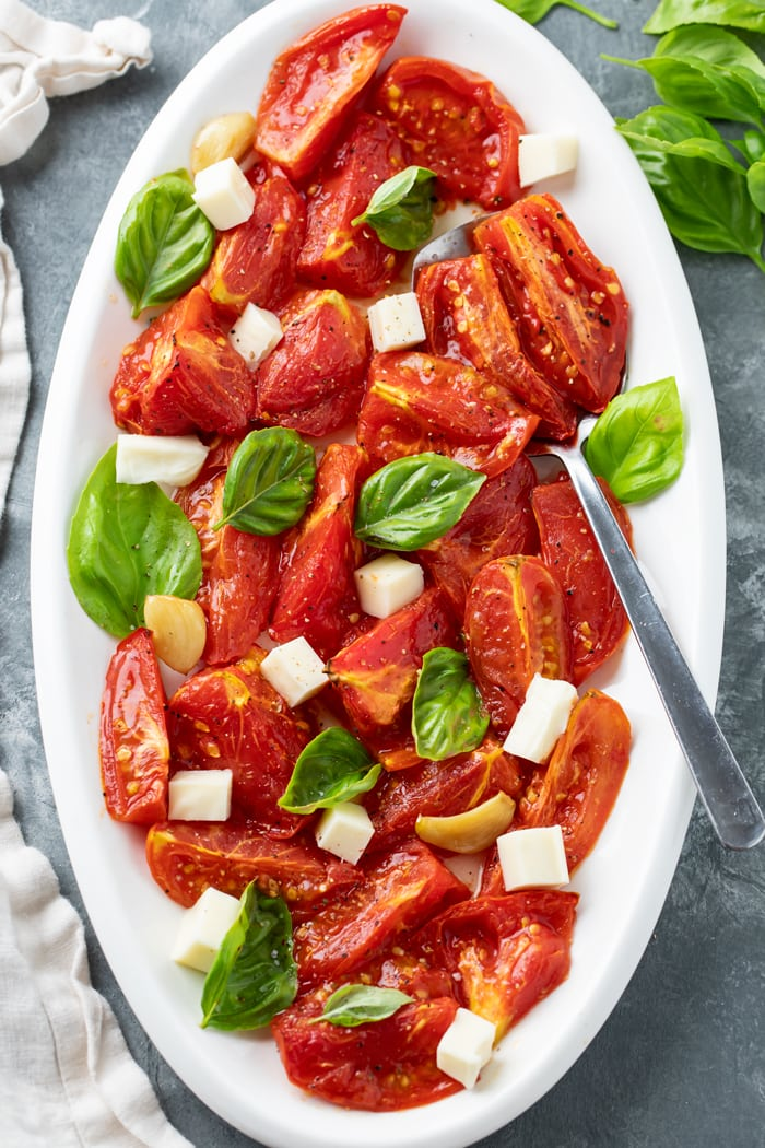 A white platter with Roasted tomatoes and basil with mozzarella, salt, and freshly cracked pepper.