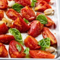 Roasted tomatoes on a baking sheet with fresh basil and garlic cloves.