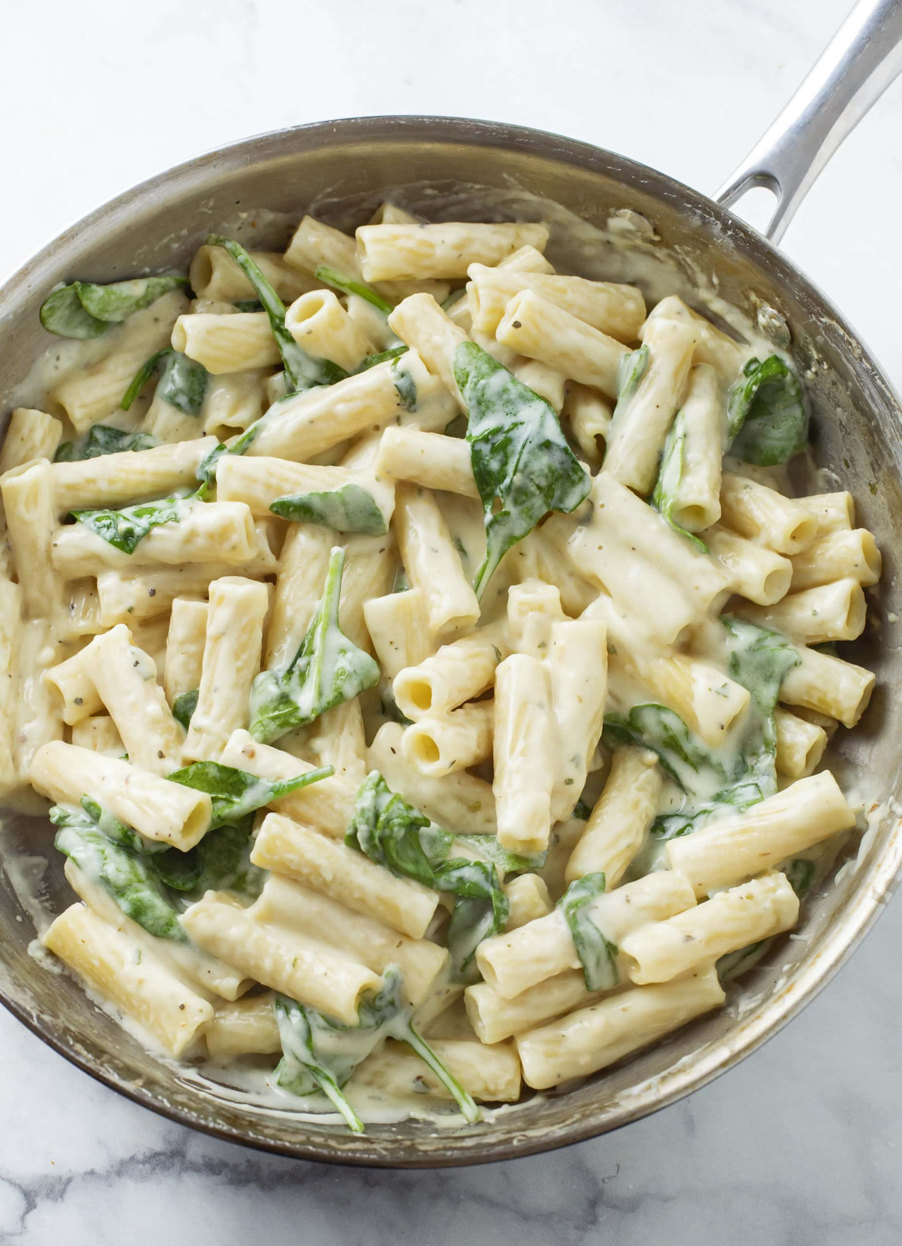 A silver skillet filled with Creamy Broccoli Pasta in a Garlic Parmesan Sauce.