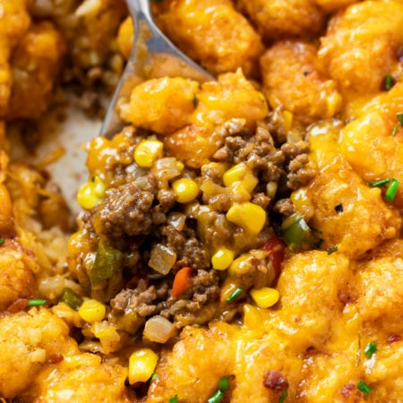 A spoon scooping up tater tot casserole with ground beef, corn, and crispy tater tots.