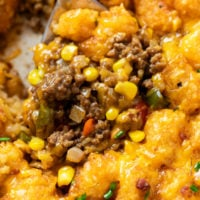 A spoon scooping up Tater Tot Casserole from a skillet with crispy tater tots and ground beef with corn.