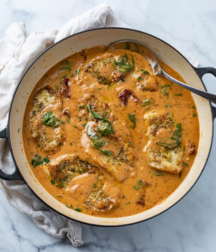 A pot of creamy Tuscan Chicken in sauce with tomatoes and spinach.