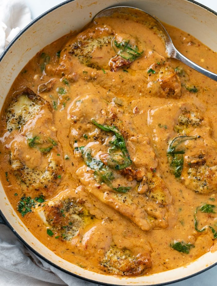 A pot of Tuscan Chicken in a creamy tomato sauce with spinach.