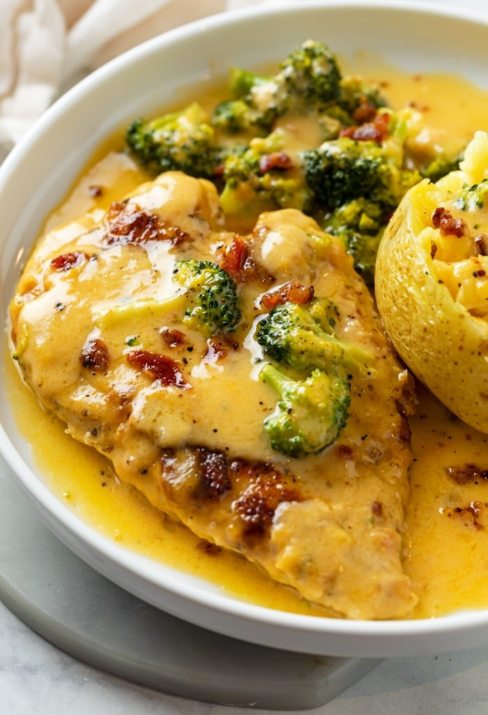A white plate with Cheese Chicken with bacon on top with broccoli and a baked potato.