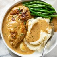 A white plate with Creamy Garlic Chicken next to mashed potatoes and green beans.