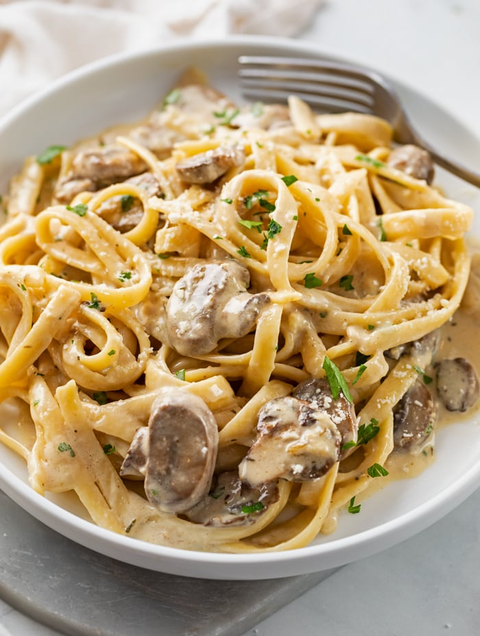 A white plate with Fettuccine Noodles in a Creamy Mushroom Sauce.