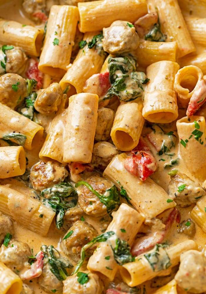 A close up view of rigatoni noodles in a Creamy Sausage Pasta with red peppers and spinach.