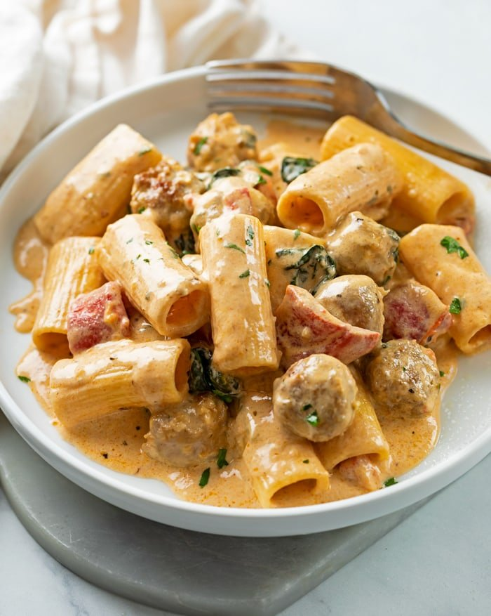 A white plate with creamy sausage pasta with roasted red peppers and rigatoni.