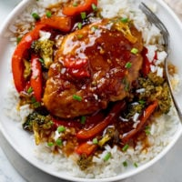 A white plate with Honey Garlic Chicken on top of rice with red bell peppers and broccoli.
