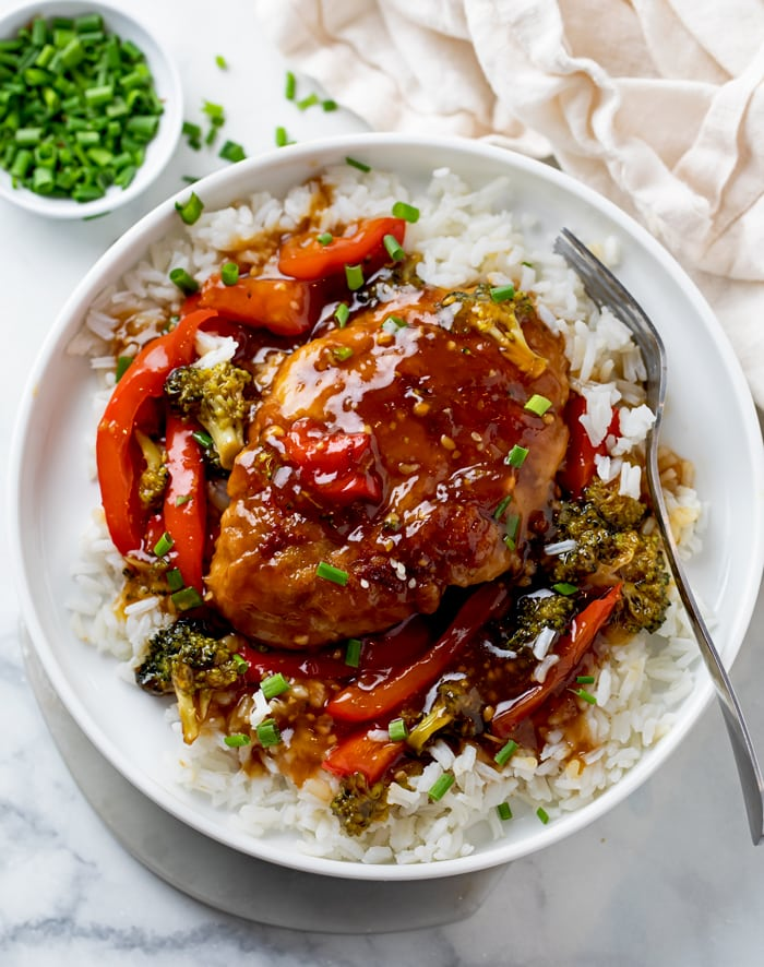 A white plate Honey Garlic Chicken on top of rice with Broccoli and Red Peppers.