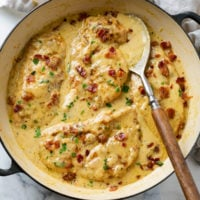 A skillet with Creamy Bacon Chicken topped with crispy bacon in a creamy sauce.