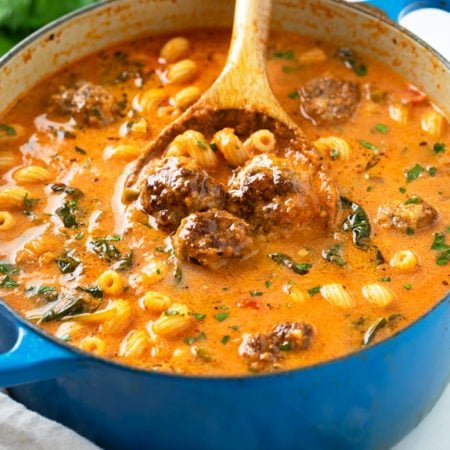 A blue dutch oven filled with Meatball Soup with meatballs, pasta, spinach, and parsley.